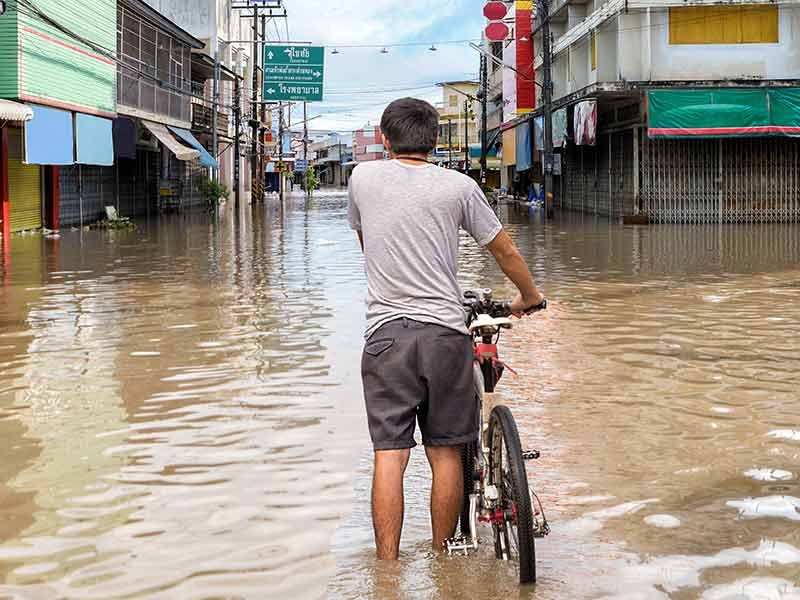 Man on a bike in flooded street - showing application of LED UVC pure water for emergency aid disaster recovery